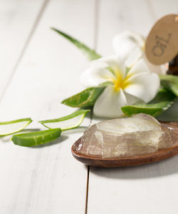 aloe vera gel on spoon with aloe vera on white wooden table